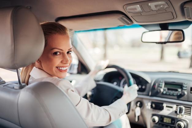 Belle femme d'affaires conduisant une voiture, souriant à la caméra.