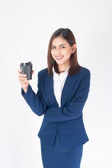 Belle femme d'affaires en costume bleu boit du café sur fond blanc