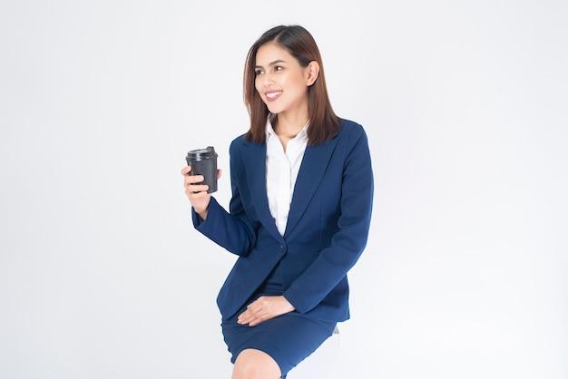 Belle femme d'affaires en costume bleu boit du café