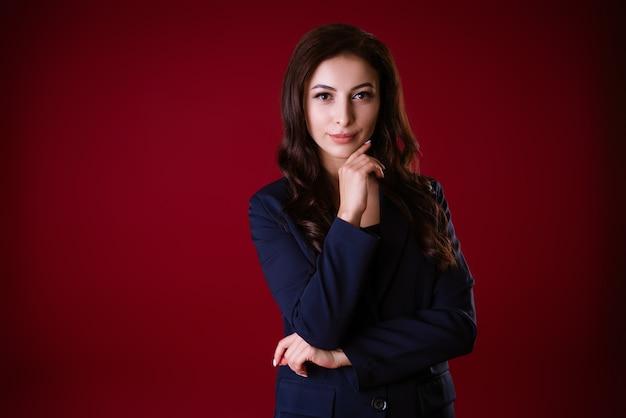 Belle femme d'affaires en costume posant sur fond rouge