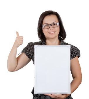 Belle femme d'affaires dans des verres tenant un tableau blanc avec un espace vide pour le vôtre design sur fond blanc
