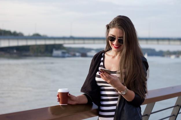 Belle femme d'affaires décontractée sur son téléphone, fille au café au coucher du soleil de la rivière