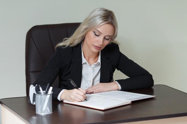 Belle femme d'affaires écrivant dans un cahier au bureau