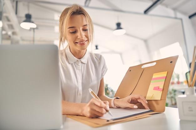 Belle femme d'affaires écrivant un rapport financier et souriant alors qu'elle était assise à la table au travail
