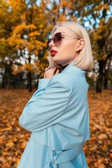 Belle femme d'affaires élégante avec des lunettes de soleil de mode dans un manteau bleu de mode marche sur fond de feuillage d'automne jaune dans le parc