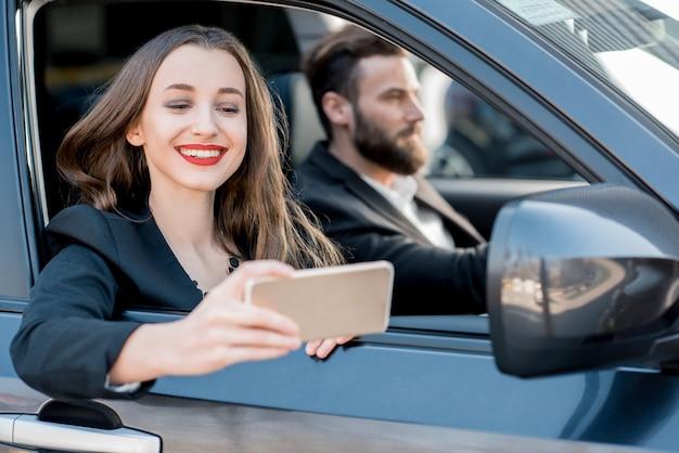 Belle femme d'affaires faisant un portrait de selfie avec un chauffeur élégant assis dans la voiture
