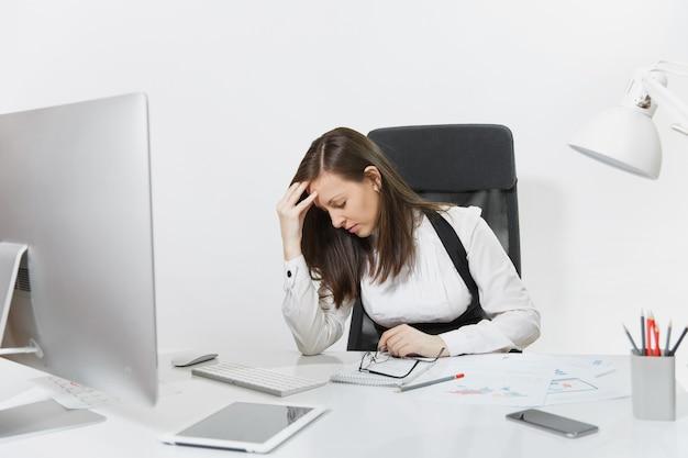 Belle femme d'affaires fatiguée, perplexe et stressée aux cheveux bruns en costume et lunettes assise au bureau, travaillant sur un ordinateur contemporain avec des documents et un moniteur dans un bureau lumineux