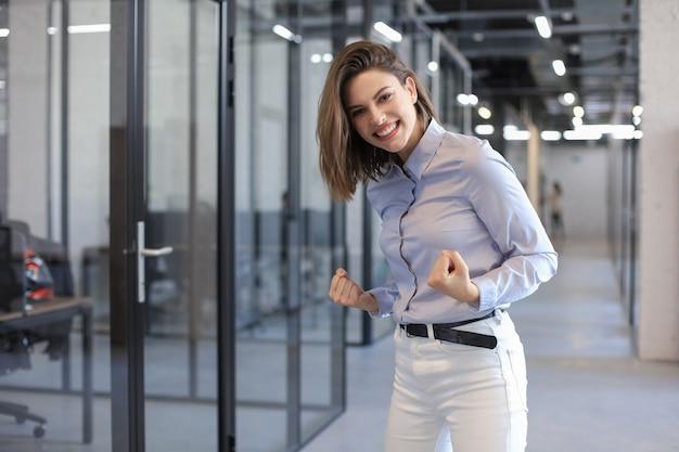 Une belle femme d'affaires garde les bras levés et exprime sa joie au bureau.
