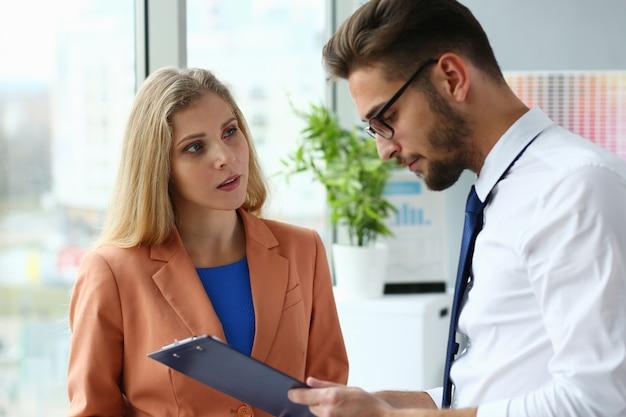 Belle femme d'affaires et homme d'affaires, analyse des documents au travail