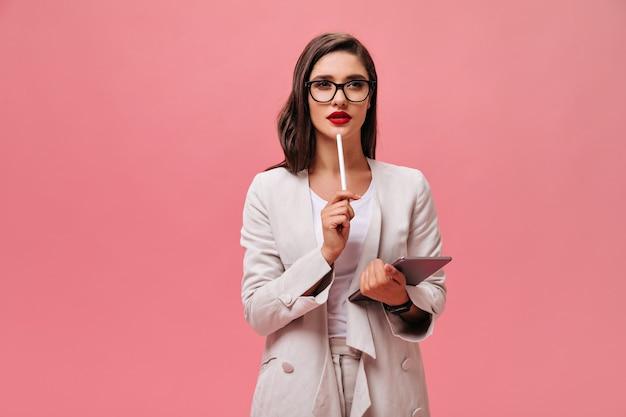 Belle femme d'affaires à lunettes et costume moderne posant pensivement avec tablette informatique sur fond rose isolé.