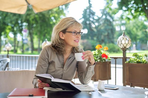 Belle femme d'affaires mature, boire du café à la pause dans le restaurant en plein air, souriant femme blonde dans des verres, chemise grise