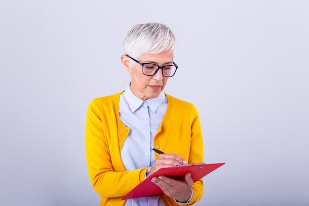 Belle femme d'affaires mature écrit dans le presse-papiers isolé sur blanc. portrait de femmes d'affaires senior avec presse-papiers et document en mains