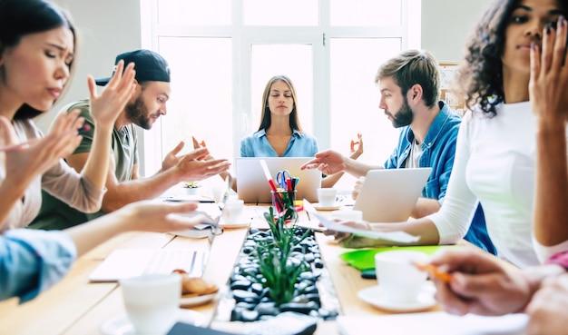 Belle femme d'affaires méditant sur le lieu de travail, ignorant le travail, n'écoutant pas les collègues ennuyeux qui lui parlaient, assise au bureau les yeux fermés et gardant son calme