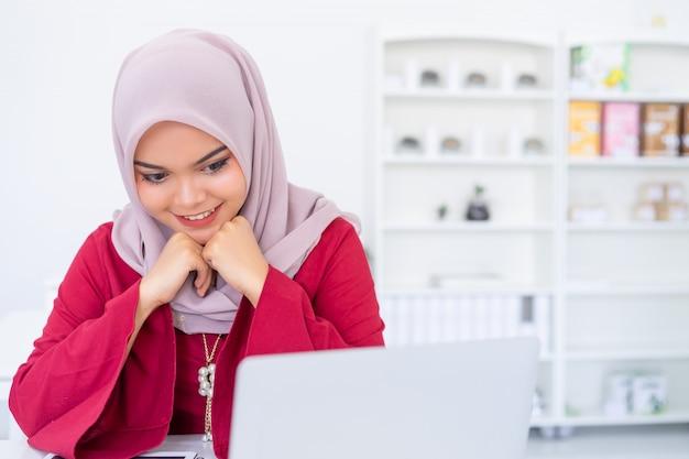 Belle femme d'affaires musulmane travaillant avec tablette au café