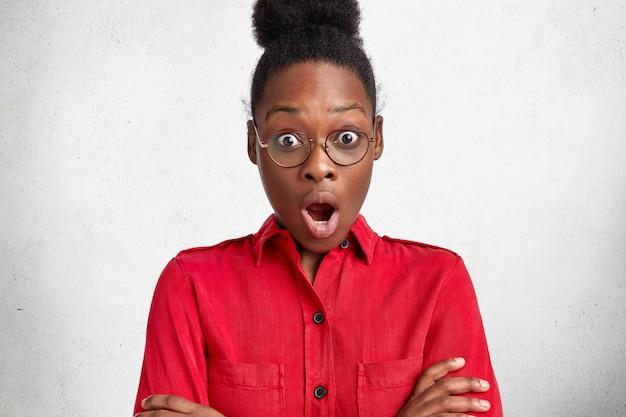 Belle femme d'affaires à la peau sombre émotionnelle porte un chemisier formel rouge et des lunettes, regarde la caméra avec une expression choquée, a la date limite pour préparer le projet d'entreprise. concept d'omg et d'ethnicité