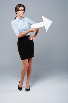 Belle femme d'affaires pointant sur l'espace de copie