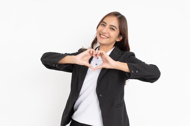 Belle femme d'affaires portant un costume noir souriant fait un geste de coeur avec les doigts