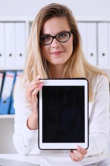 Belle femme d'affaires portant des lunettes portrait au bureau tenant une tablette