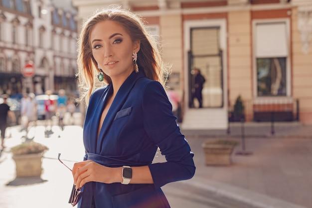 Belle femme d'affaires portant une veste bleue dans la rue piétonne de style luxe sexy