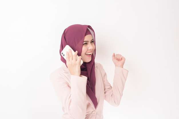 Belle femme d'affaires avec portrait hijab sur mur blanc