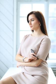 Belle femme d'affaires posant au bureau intérieur