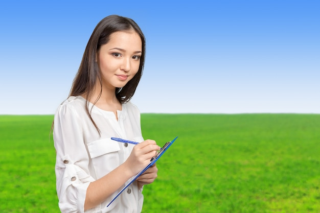 Belle femme d'affaires prenant des notes sur son presse-papiers