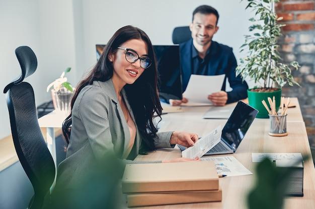 Belle femme d'affaires regardant l'avant et souriant tout en travaillant au bureau
