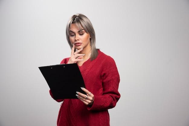 Belle femme d'affaires regardant le presse-papiers sur fond gris.