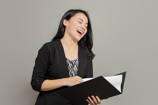 Belle femme d'affaires riant tout en tenant le dossier