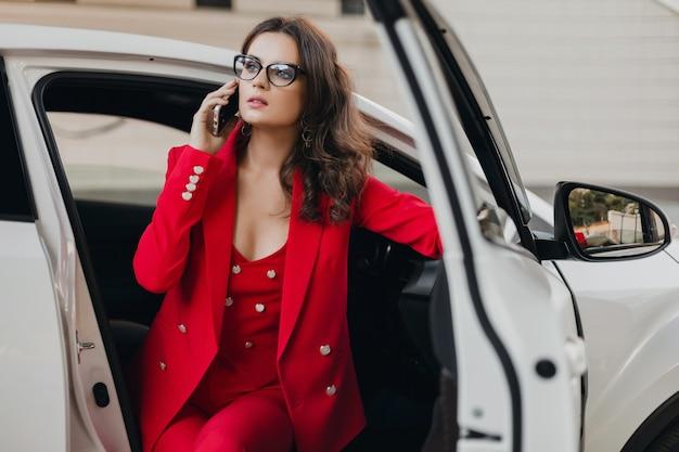 Belle femme d'affaires riche sexy en costume rouge assis dans une voiture blanche, portant des lunettes parlant au téléphone, style femme d'affaires