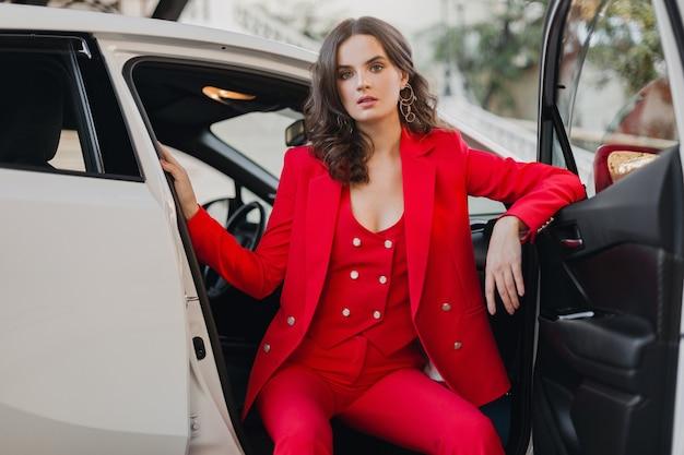 Belle femme d'affaires riche sexy en costume rouge posant dans une voiture blanche