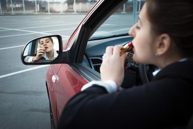 Belle femme d'affaires s'asseyant dans la voiture et appliquant le rouge à lèvres