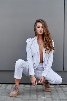 Belle femme d'affaires se tient devant un mur dans un costume blanc