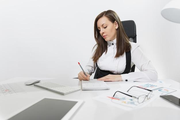 Belle femme d'affaires sérieuse aux cheveux bruns en costume et lunettes assise au bureau, travaillant à l'ordinateur avec un moniteur moderne et des documents dans un bureau léger, écrivant dans un ordinateur portable