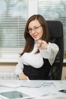 Belle femme d'affaires souriante aux cheveux bruns en costume et lunettes assise au bureau avec tablette, travaillant sur ordinateur avec des documents dans un bureau léger