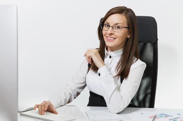 Belle femme d'affaires souriante aux cheveux bruns en costume et lunettes assise au bureau, travaillant à l'ordinateur avec un moniteur moderne avec des documents dans un bureau léger