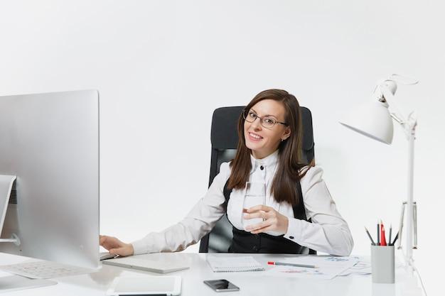Belle femme d'affaires souriante aux cheveux bruns en costume et lunettes assise au bureau avec un verre d'eau pure, travaillant à l'ordinateur avec un moniteur moderne avec des documents dans un bureau lumineux
