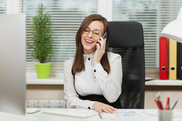 Belle femme d'affaires souriante en costume et lunettes assise au bureau, travaillant sur un ordinateur contemporain avec des documents dans un bureau léger, parlant au téléphone portable, menant une conversation agréable