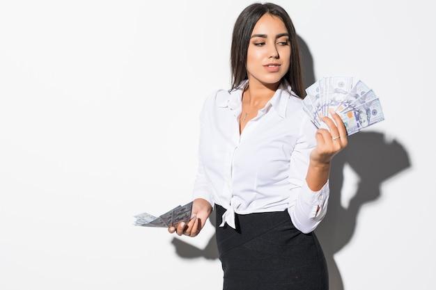 Belle femme d'affaires de succès tenant des billets en dollars sur blanc