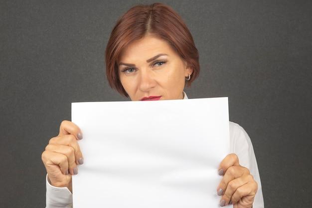 Belle femme d'affaires tenant une feuille de papier blanc dans ses mains