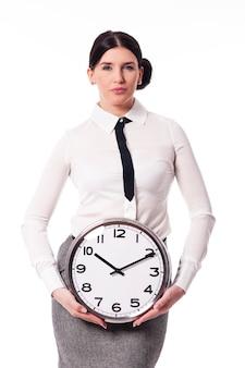 Belle femme d'affaires tenant une horloge