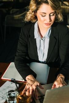 Belle femme d'affaires travaillant sur un ordinateur portable au restaurant