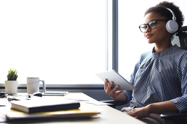 Belle femme d'affaires travaille à l'aide d'une tablette numérique tout en étant assise dans un bureau créatif.