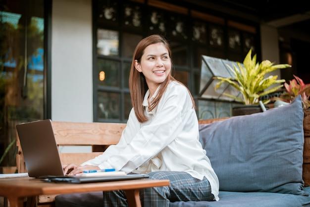 Belle femme d'affaires travaille avec son ordinateur portable dans un café