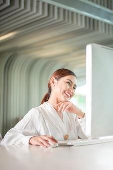 Belle femme d'affaires travaille avec son ordinateur