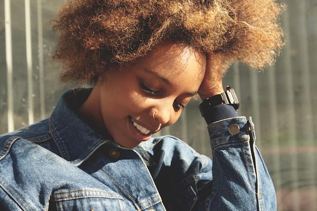 Belle femme africaine avec anneau dans le nez, posant à l'extérieur contre un mur gris, avec une expression joyeuse et heureuse, regardant vers le bas, touchant ses cheveux bouclés, passant une journée en plein air