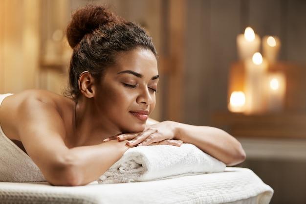Belle femme africaine au repos relaxante dans une station thermale avec les yeux fermés.
