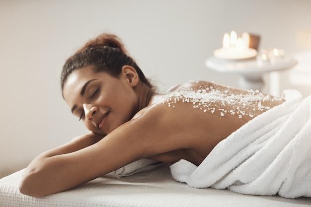 Belle femme africaine au repos relaxante avec du sel de mer sur le dos dans le salon spa.