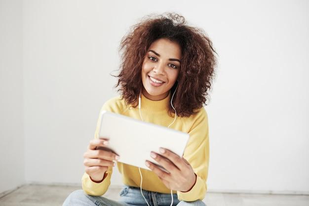 Belle femme africaine dans les écouteurs souriant tenant la tablette assis sur le sol