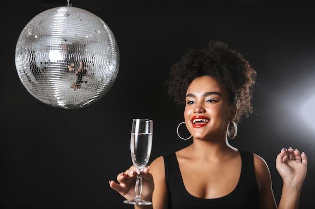 Belle femme africaine debout avec boule disco argent isolé sur espace noir